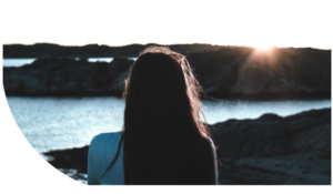 Awareness - Young woman thinking by sea during sunrise.
