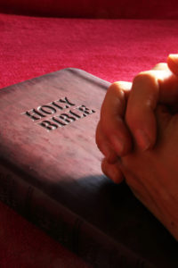 His word the holy bible. Hands folded in prayer on closed Bible.
